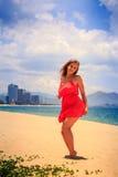 红色的白肤金发的女孩在沙子接触熟悉内情的下面风赤足站立 免版税库存照片