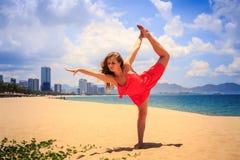 红色的白肤金发的女孩在沙子的体操位置腿标度站立 库存照片