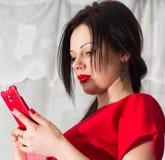 红色的美丽的女孩与一个明亮的电话 免版税库存照片