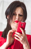红色的美丽的女孩与一个明亮的电话 库存图片