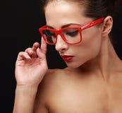 红色的美丽的构成妇女注视看的玻璃下来 特写镜头 免版税库存图片