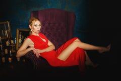 红色的美丽的金发碧眼的女人在一把淡紫色椅子 库存图片