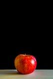 红色的苹果一个木板有黑背景 库存图片