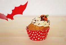 红色的蝙蝠杯形蛋糕装饰用奶油和小杏仁饼南瓜在万圣夜 免版税库存照片