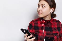 红色的行家女孩检查了衬衣安排头发编辫子在尾巴拿着手机听音乐或audiobook的与耳机 免版税库存图片
