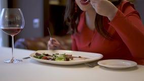 红色的逗人喜爱的妇女在餐馆和吃坐可口沙拉 影视素材