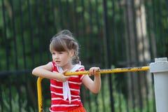 红色的逗人喜爱的小女孩在环形交通枢纽旋转 库存图片