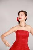 红色的青少年的女孩与在头发的花 图库摄影