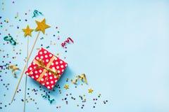 红色的顶视图加点了礼物盒、金黄不可思议的鞭子、五颜六色的五彩纸屑和丝带在蓝色背景 庆祝概念查出的白色 Co 免版税库存照片