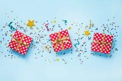 红色的顶视图加点了礼物盒、金黄不可思议的鞭子、五颜六色的五彩纸屑和丝带在蓝色背景 庆祝概念查出的白色 免版税库存图片