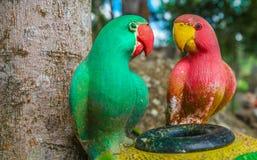 红色的鹦鹉和绿色雕象在庭院里 库存图片