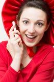 红色的年轻愉快的惊奇的妇女与手机 免版税图库摄影