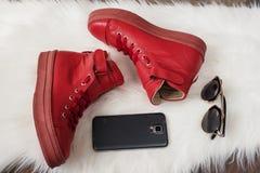 红色皮革运动鞋,手机,在一张白色地毯的太阳镜 免版税图库摄影