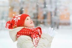 红色盖帽捉住的落的雪花的小女孩 圣诞节ba 免版税库存图片