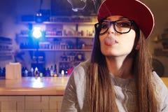 红色盖帽烟的年轻俏丽的妇女一根电子香烟在vape商店 特写镜头 免版税库存图片