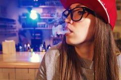 红色盖帽烟的年轻俏丽的妇女一根电子香烟在vape商店 特写镜头 库存照片