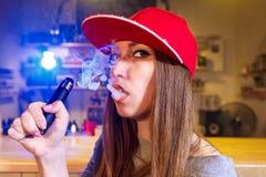 红色盖帽烟的年轻俏丽的妇女一根电子香烟在vape商店 特写镜头 免版税库存照片
