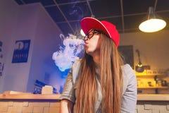红色盖帽烟的年轻俏丽的妇女一根电子香烟在vape商店 免版税图库摄影