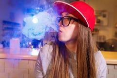 红色盖帽烟的年轻俏丽的妇女一根电子香烟在vape商店 免版税库存照片