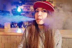 红色盖帽烟的年轻俏丽的妇女一根电子香烟在vape商店 库存照片