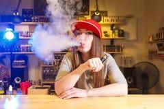 红色盖帽烟的年轻俏丽的妇女一根电子香烟在vape商店 免版税库存图片