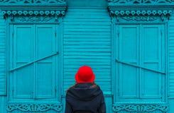 红色盖帽的妇女看蓝色老村庄房子在俄国村庄 免版税库存图片