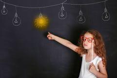 戴红色眼镜的聪明的孩子把一个手指指向被点燃的灯 免版税库存图片