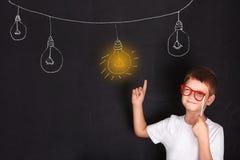 戴红色眼镜的聪明的男孩把一个手指指向被点燃的灯 库存图片