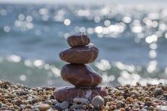 红色石头和小卵石堆、和谐和平衡,在海岸的一个石石标 免版税库存照片