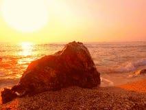 红色石海岸,沙子,在狂放的海滩的日落 免版税图库摄影