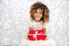 红色礼品 一个小白白种人女孩的图片有拿着有白色丝带的卷发的红色礼物盒反对明亮的白色sil 免版税库存图片