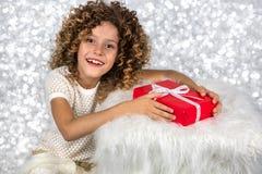 红色礼品 一个小白白种人女孩的图片有拿着有白色丝带的卷发的红色礼物盒反对明亮的白色sil 免版税库存照片