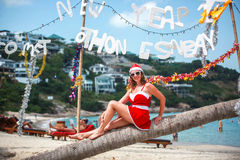 红色礼服、太阳镜和圣诞老人帽子的逗人喜爱的白肤金发的妇女坐棕榈树在异乎寻常的热带海滩 节假日概念 免版税库存照片