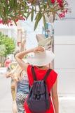 红色礼服、白色帽子和背包的妇女走在镇里的 免版税库存图片