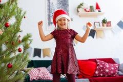 红色礼服和圣诞老人帽子的愉快的女孩期待在红色装饰的圣诞节 库存图片