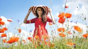 红色礼服和大帽子的愉快的年轻女人享受自然的 在鸦片领域的秀丽女孩室外步行   股票视频