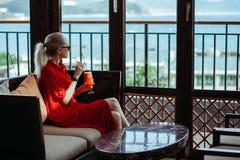 红色礼服和太阳镜的美丽的年轻白肤金发的女孩喝从一块玻璃的红色鸡尾酒在一个开放大阳台  库存图片