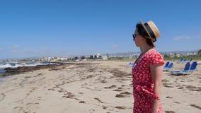 红色礼服和帽子身分的年轻美女单独在与sunbeds的空的海滩 与猛烈的波浪和风的沙滩 股票视频