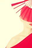 红色礼服和爱好者的美丽的妇女 免版税图库摄影