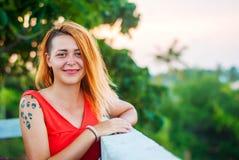 红色礼服和被刺字的微笑的美丽的红发女孩在夏天餐馆的游廊笑 免版税库存图片