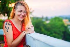 红色礼服和被刺字的笑的美丽的红发女孩在夏天餐馆的游廊 免版税库存图片