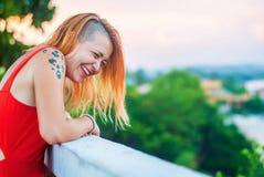 红色礼服和被刺字的笑的美丽的红发女孩在夏天餐馆的游廊 免版税库存照片