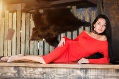 红色礼服和长的头发的性感的美丽的深色的妇女有看照相机说谎的微笑的 免版税库存照片