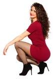 红色礼服和高跟鞋的卷曲可爱的愉快的妇女 库存图片