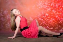 红色礼服姿势的女孩在演播室 库存照片