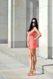 红色礼服摆在的可爱的深色的妇女室外 免版税图库摄影