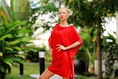红色礼服摆在的年轻性感的白肤金发的妇女室外 免版税图库摄影