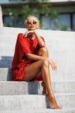 红色礼服摆在的年轻性感的白肤金发的妇女室外 库存照片