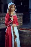 红色礼服有围裙的和妇女的Townswoman在街道上 免版税库存照片