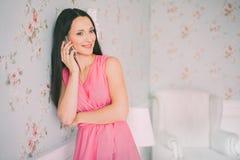红色礼服电话谈话的少妇 女孩画象有智能手机的 库存照片